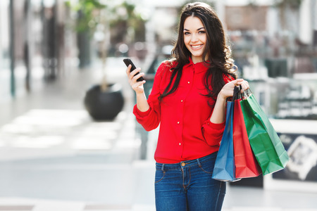 Nice girl in mall with shopping bags and phone