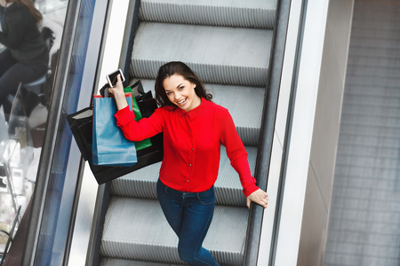 Beautiful girl on escalator with shopping bags Фото со стока