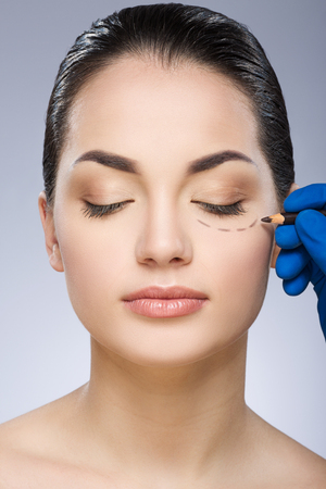 Doctor drawing dashed line under eye