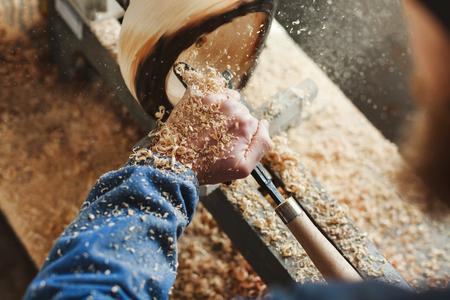 Ein Mann, der mit Holzschnitzinstrumenten arbeitet