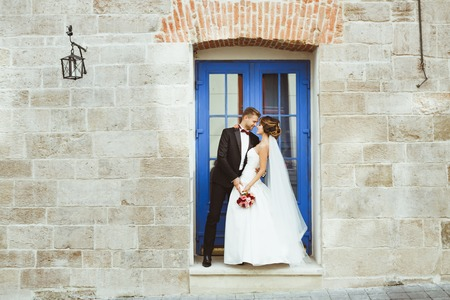 Bride and bridegroom standing near blue door 写真素材