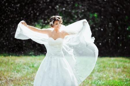 Bride standing under rain