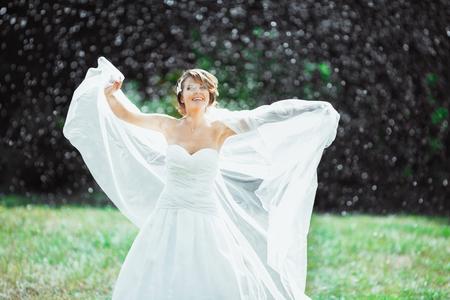 Smiling bride standing under rain
