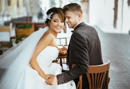 Bride and groom sitting on chairs