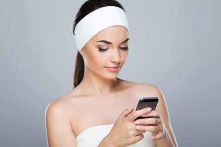 Model with white headband holding phone