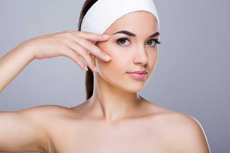 Young woman with white headband touching face Standard-Bild