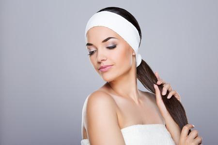 Frau mit weißem Stirnband, die ihren Pferdeschwanz hält Standard-Bild