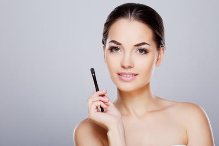 Girl holding with brush near face Imagens