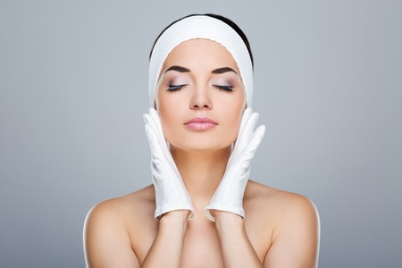Woman touching face with white gloves Stockfoto