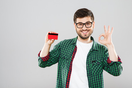 Man holding red credit card and showing ok