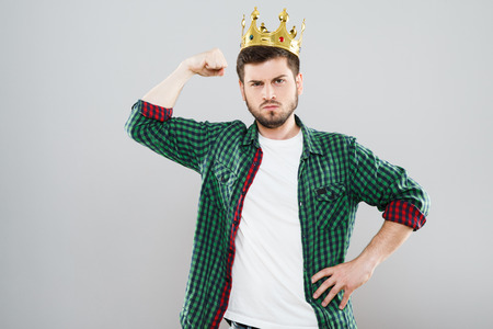Frowning man in crown showing strength