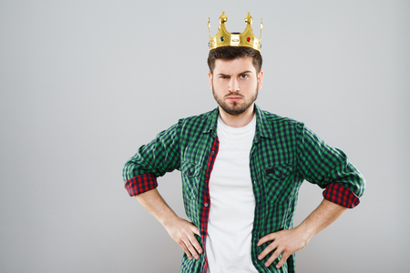 Frowning young man in green checkered shirt and crown