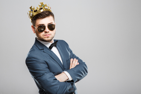 Serious man in crown Фото со стока