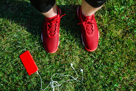 Red sneakers, phone on grass