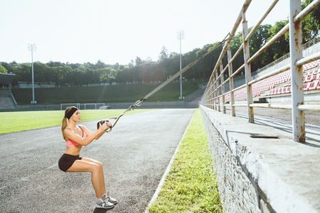 Woman squatting with training loop Stockfoto