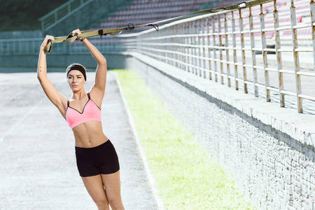 Sporty woman doing exercises with training loop