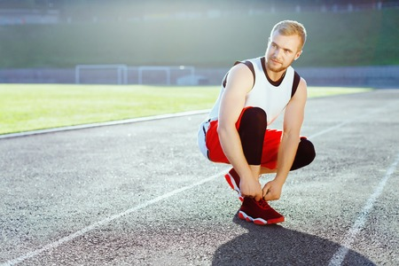 Sportsman crouched in red sneakers