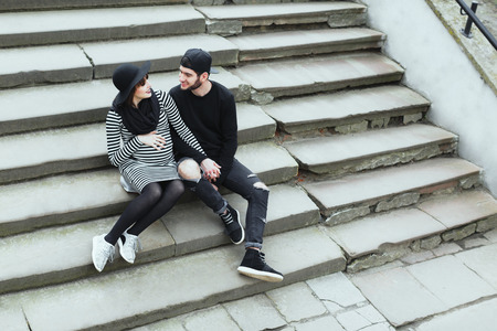 Man and pregnant girl sitting on stairs