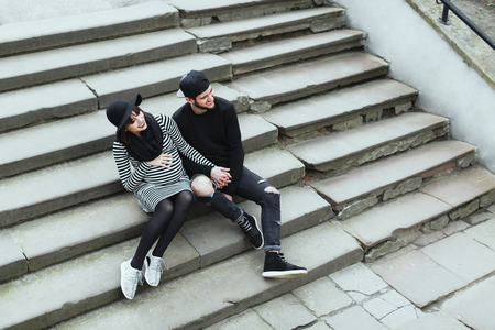 Pregnant girl and man sitting on stairs