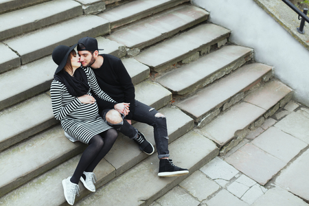 Man and pregnant woman sitting on stairs