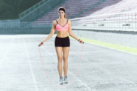 Girl jumping on skipping rope on stadium