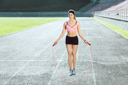 Sporty girl jumping on skipping rope on stadium