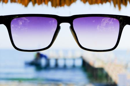 Black sunglasses at sea background