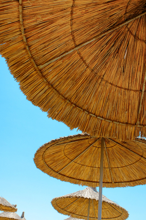 Three beach umbrellas made of straw at blue sky background