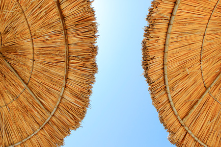 Beach umbrellas made of straw at blue sky background Banque d'images