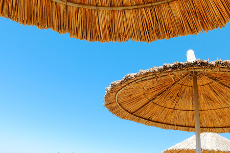 Three beach umbrellas made of straw at blue sky background