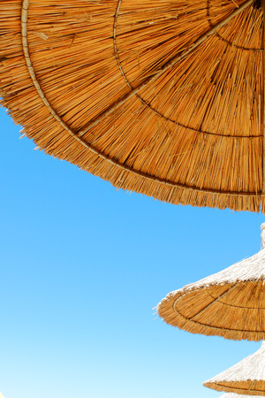 Beach umbrellas made of straw at blue sky background 写真素材 - 122493988