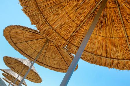 Beach umbrellas made of straw at blue sky background 写真素材