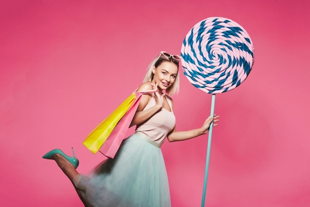 Beautiful  model with sweets at pink background
