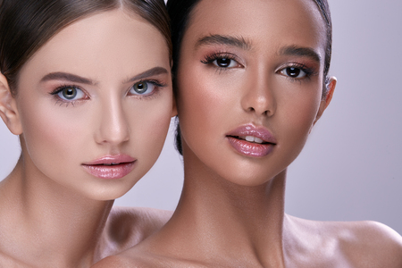 two beautiful girls with perfect skin looking to the camera