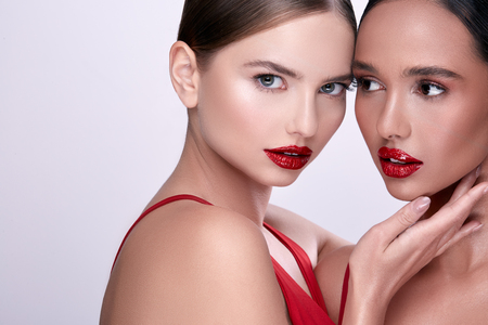 two beauty faces with red lipstick, handsome women on grey background Banco de Imagens