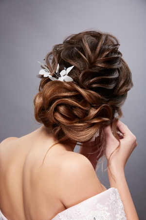 brides head with perfect hairstyle putting on earings Banco de Imagens