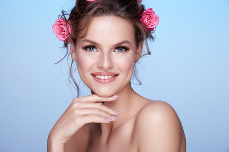Pretty woman at studio background with flowers