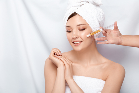 beautician holding syringe near womans face in bath towel and open shoulders, woman getting beauty injection isolated on white