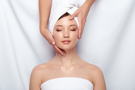 beauty master holding womans face that lying down on white, head and face treatment for women, client of spa theraphy 写真素材 - 123710648