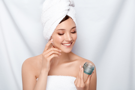 young and beautiful woman smiling and looking on the cream that she applying, after shower girl putting on moisturizer