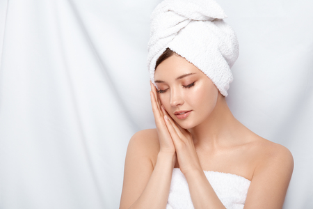 young and beautiful female in bath towel holding her hands near face with her eyes closed, pretty woman after treatment procedures Banque d'images