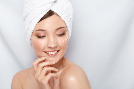 beautiful girl in bath towel with cream under eye touching her face and looking down to the side, copy space, pretty lady after spa
