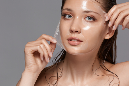 beautiful woman removing peeling mask from her face and looking to the camera, copy space, moisturizing effect