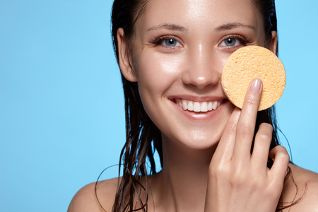 close-up portrait of pretty girl with wet hair washing face with beige sponge and smiling, copy space, fresh and beauty concept