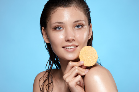 pretty girl with wet face keeps beige sponge near her shoulder and smiling to the camera, fresh and beautiful woman face after bath