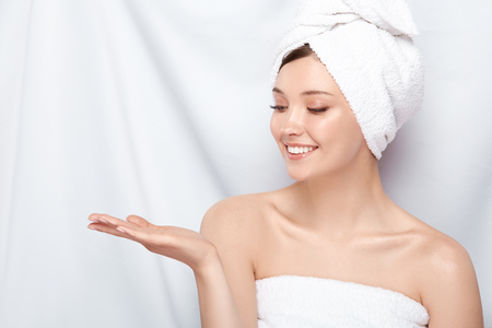 beautiful girl with perfect skin and in bath towel looking to her hand, copy space, young and fresh natural face after spa Standard-Bild