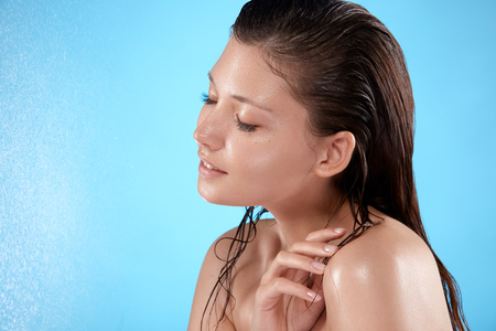 happy girl with wet hair and face touching her shoulder with eyes closed, girl with water splashes, fresh face on isolated on blue