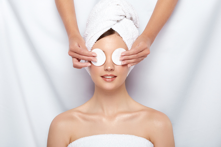beautician closing womans eyes with two cotton pads, happy and treated customer of spa procedures, skin care theraphy, relaxation in clinic