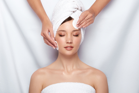 beautician wiping womans face with cotton pads, girl gets facial treatment, female arms cleans body with two sponges in spa 写真素材