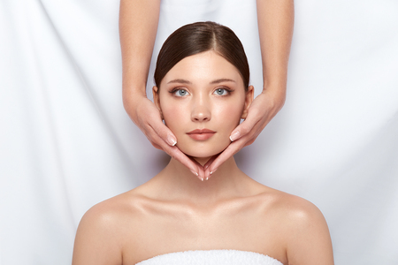 two arms holding womans face with her eyes open in spa room, copy space, pretty girl on skin care treatment 写真素材 - 123710961